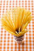 Spaghetti in beaker on checked tablecloth