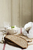 Slices of wholemeal bread with a small dish of soft cheese