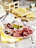 Plate of cold cuts (ham, pastrami) and gherkins