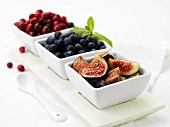 Figs, blueberries and cranberries in dishes