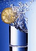 Wasser spritzt aus Glas mit Zitronenscheibe