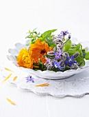 Borage flowers, marigolds, verbena and basil on plate