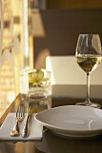 Place-setting with glass of white wine in restaurant