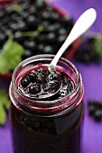Blackcurrant jam in jar with spoon