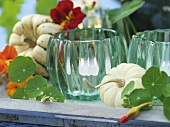 Autumn table decoration: candles in glasses, gourds, nasturtiums