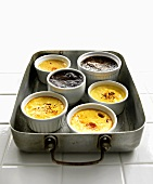 Several dishes of crème caramel in bain-marie