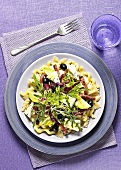Pasta with ham, cheese, olives and salad leaves