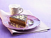 Piece of chocolate cake with flaked almonds, cappuccino
