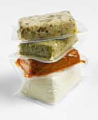 Various types of tofu in plastic packaging, stacked