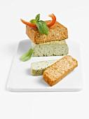 Basilikum-Tofu und Rosso-Tofu angeschnitten mit Basilikum und Paprikastreifen auf Porzellanplatte