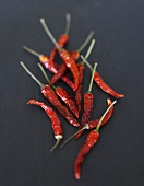 Several dried chillies on slate