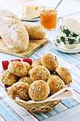 Wholemeal rolls in bread basket, bread, marmalade and cheese