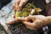 Hands holding smoked bass stuffed with lemon, thyme and rosemary