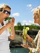 Two women with refreshing cucumber drinks (out of doors)