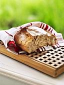 Broken bread in tea towel on breadboard