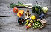 Autumn vegetables, fruit, mushrooms and chestnuts on wood