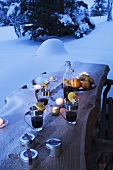 Mulled wine on snowy wooden table in garden
