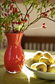 Vase of rose hips and dish of pears on a table