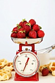 Strawberries on kitchen scales, waffles beside them
