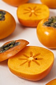 Several persimmons with slices removed