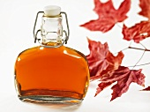 A bottle of maple syrup and red maple leaves