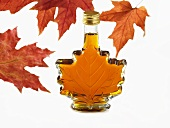 A bottle of maple syrup in shape of maple leaf with red maple leaves