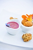 Vegetable balls with raspberry sauce and edible flowers
