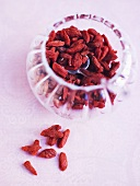 Goji berries in and beside a small glass bowl