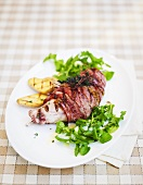 Bacon-wrapped rabbit leg with wild herb salad