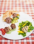 Meat kebab, meatballs & pork fillet with vegetables, pesto & salad leaves