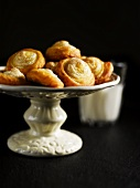 Quark pastry pinwheels with meringue on cake stand, glass of milk