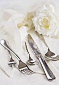 Cutlery on napkins with white rose