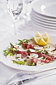 Beef carpaccio with button mushrooms on elegantly laid table