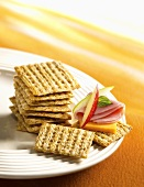 Crackers, one topped with cheese and ham
