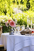 Bread, wine glasses and jug of roses on laid table in garden