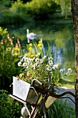Old bicycle with planter by garden pond