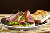 Roast duck breast with gherkin and lettuce on toast