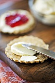 Spreading oatcake with soft cheese