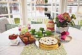 Rhubarb pie, rhubarb muffins and tea on springtime table
