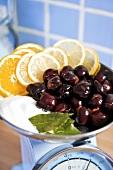 Cherries, sugar and lemon slices on scales