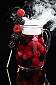 Berry punch in glass jug with dry ice mist