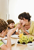 Mother having breakfast with two children