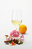 Glass of white wine and various aromatic ingredients
