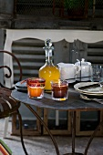 Jam, fruit juice, candle and crockery on metal table