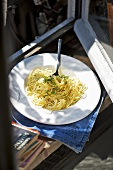 Spaghetti with herbs on plate by window