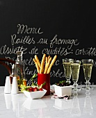 Appetisers & sparkling wine on marble slab in front of slate menu board