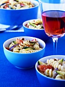 Pasta salad in blue bowls and glass of rosé wine on table