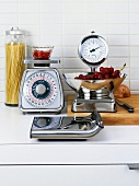 Various kitchen scales, onion, fruit and spaghetti