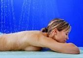 Frau unter Wasserstrahl im Spa