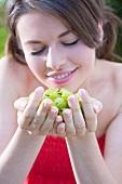 Junge Frau mit einer Handvoll Stachelbeeren